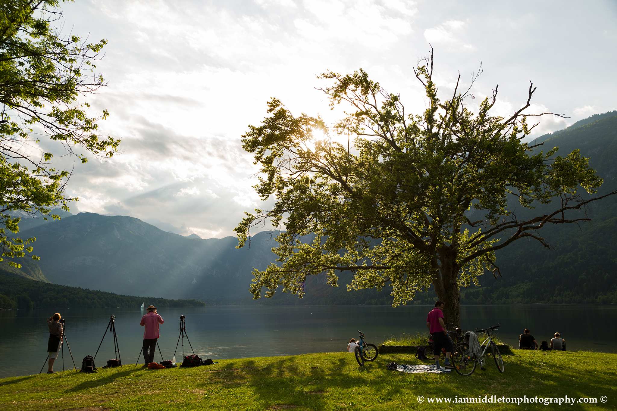 Workshop participants photographing beautiful light and clouds scattering over Bohinj Lake,Triglav National Park, Slovenia.